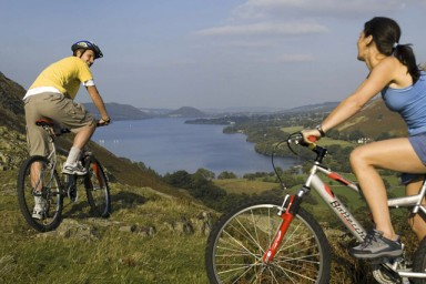 Cyclists taking in the view across Ullswater from hilltop near Martindale in the Lake District, Martindale, Cumbria, England.